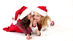 Cute festive girls lying on floor telling secrets Footage