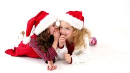 Cute festive girls lying on floor telling secrets Footage