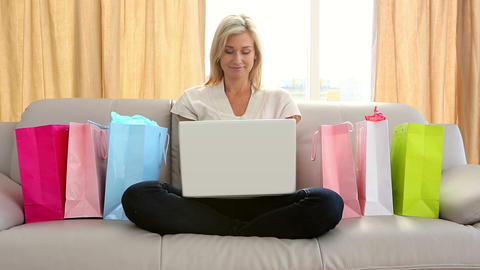 Pretty blonde sitting on couch shopping online surrounded by bags Footage
