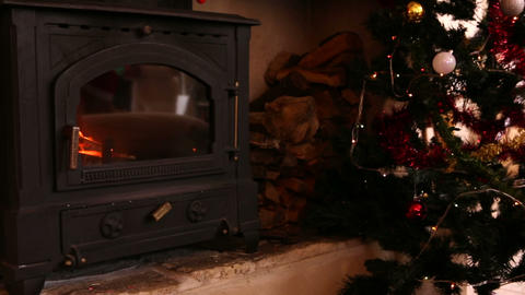 Fire burning in fireplace beside christmas tree Footage