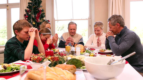 Three generation family saying grace before christmas dinner together Live Action