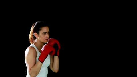 Fit brunette punching with gloved fists Footage