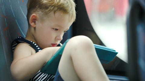 Little Boy In Car Using Tablet Computer Footage