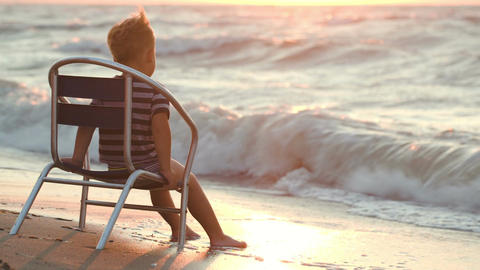 Boy sitting alone on the chair by sea Footage