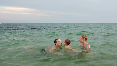 Happy Family Of Three Playing Ball In Sea stock footage