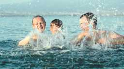 Family Of Three Splashing Water In Sea Footage