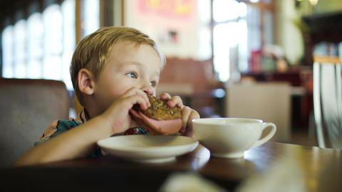 Little Boy Eating Sandwich In A Cafe Footage