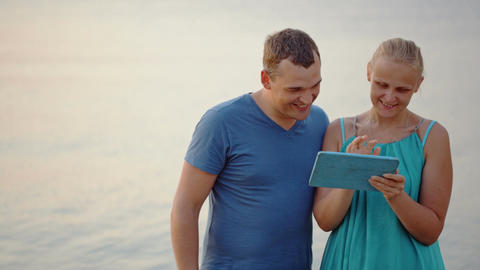 Young Couple Using Tablet Computer By The Sea Footage