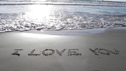 i love you written on sand sunset waves beach roma Stock Video Footage