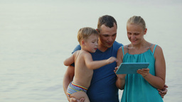Parents And Little Son With Pad By The Sea Footage
