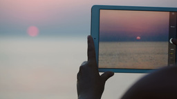 Taking pictures of sunset over sea with touch pad Footage