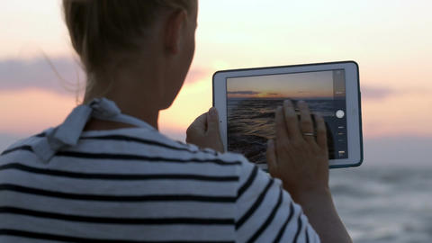 Woman making photos of sea waves with pad Footage