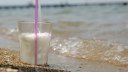 Pouring fizzy drink into glass on the sand Footage