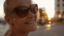 Smiling woman in sunglasses outdoor during sunset Footage