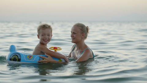 Mother and son having fun playing in the sea Footage