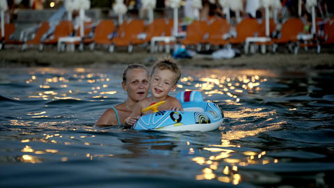 Son with rubber ring and mother bathing in sea Footage