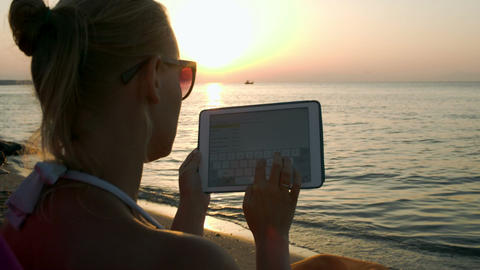 Woman typing on pad sitting by sea at sunset Footage