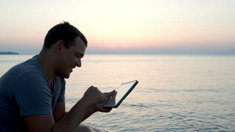 Young man by the sea typing message on pad Footage