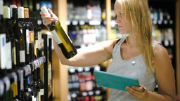 Woman choosing wine using pad Footage