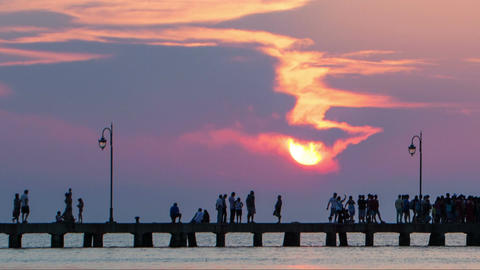 Timelapse of people walking on pier at sunset Footage