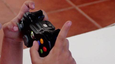 Kid's hands on a Xbox remote Live Action