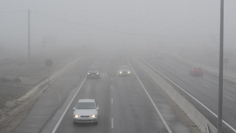 Cars drive in dense fog Footage
