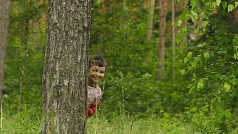 Cheerful little girl hiding behind a tree in the f Footage