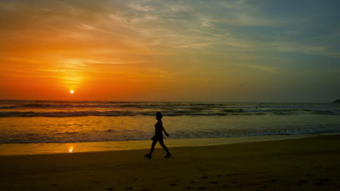 Sunset on tropical beach. A woman walks along the  Footage
