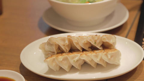 person pours gyoza sauce and eats one with chopsti ライブ動画