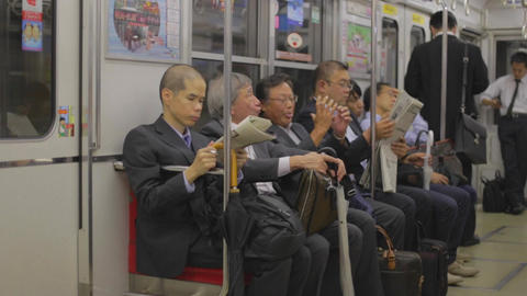 Japanese businessmen talk and read newspapers on t Footage