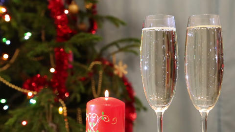 Glasses With Champagne And Candle Against Christma stock footage