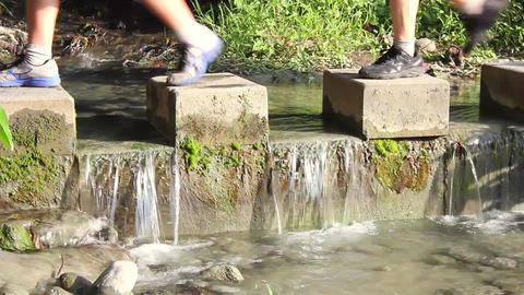 People walking across stones step with flowing wat Footage