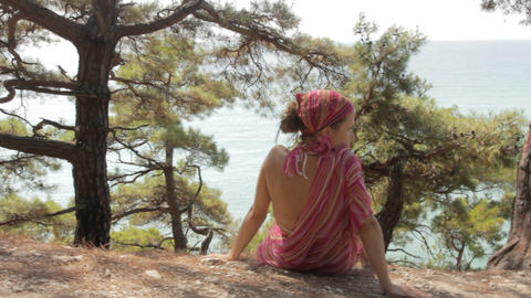 Young woman sits on a cliff against sea Stock Video Footage