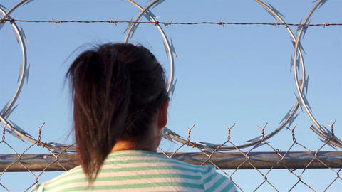 Woman Climing Razor Wire Fence Footage