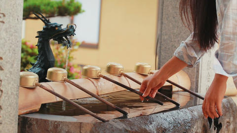 Young Woman washing her hands at a traditional shr Footage