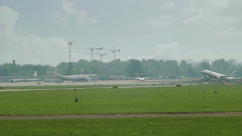 plane taxiing in distance with another crossing ov Footage