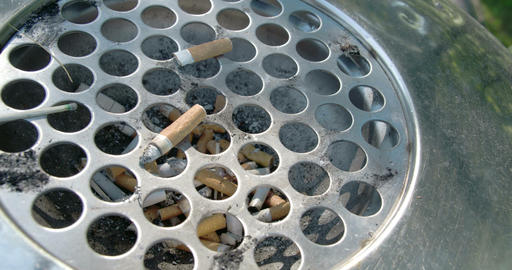 A cigarette bin or ahstray with lots of cigs insid Footage