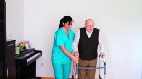 Carer Helping Elderly Senior Man Using Walking Live Action
