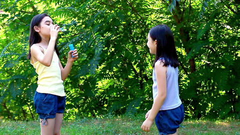 Little girls blowing soap bubbles in the park 1 Footage