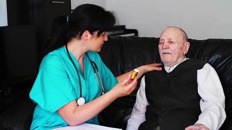 Nurse giving pills to a senior man Footage