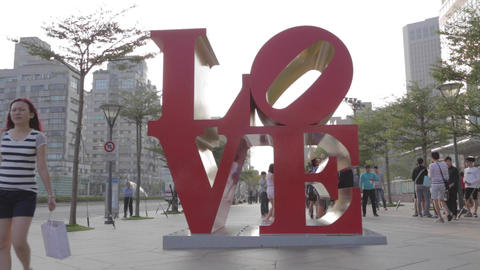 young Asian lady at love sculpture at Taipei 101 Footage