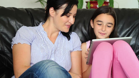 Smiling mother and daughter using tablet computer Footage
