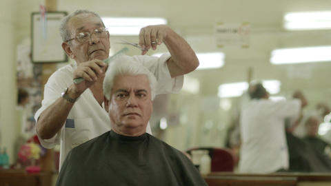 Elderly Barber Giving Haircut To Customer in Beauty Parlor Stock Video Footage