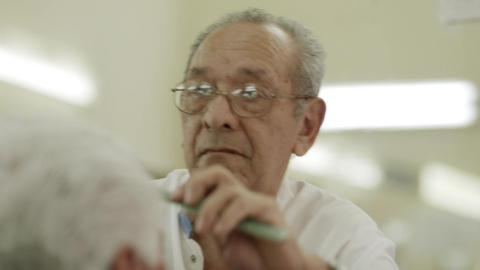 Elderly Barber Giving Haircut To Customerin Beauty stock footage