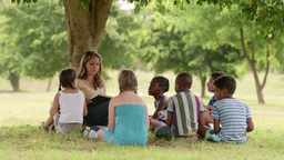 People And Education Young Teacher Reading Book To Kids Group of Children Live Action