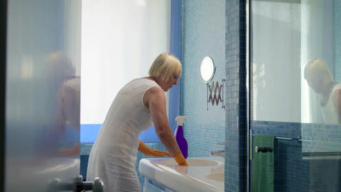 Senior Woman Doing Chores In Bathroom At Home stock footage