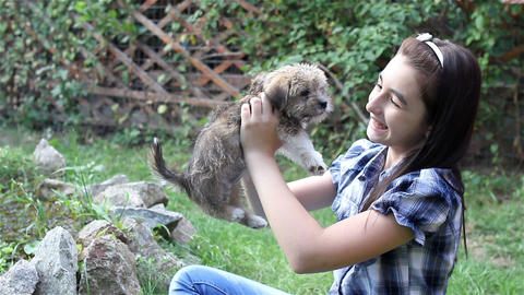 Girl cuddling a puppy outdoors in the garden 3 Footage