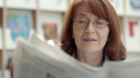 Portrait of old woman with eyeglasses reading newspaper Footage