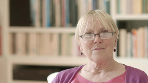 Portrait of happy retired caucasian woman reading book with eyeglasses Footage