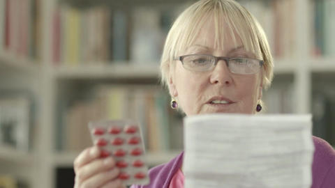 Elderly caucasian woman with medicine and reading drug prescription Footage